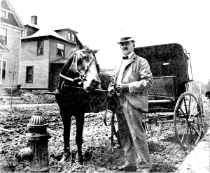Dr. George Sherman Peck standing on a muddy street with his horse and buggy.